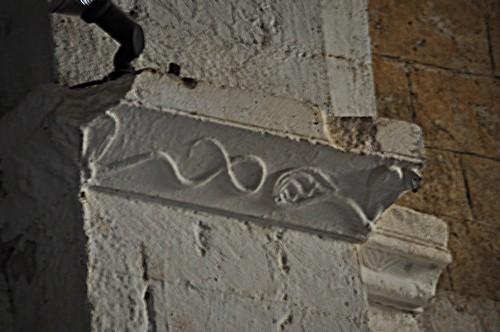 Curieux motif formé de deux serpents qui semblent sortir de masques de feuillages.